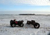 A 2005 Polaris 800 ATV pulling a 1950's vintage spreader w/ GPS attached
